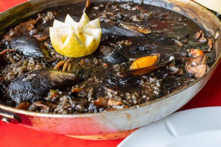Close-up of black rice with squid –in ink– mussels, clams and other seafood. Presented in paellera.