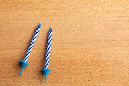 2 blue birthday candles on wooden background. For birthday greeting card. Space to insert text. Very colorful, with blue, red, yellow and white. For birthday greeting card.
