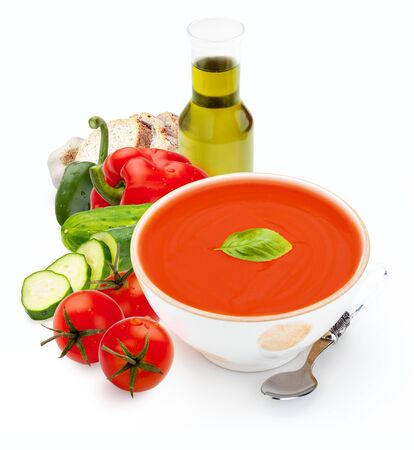 Bowl with gazpacho and with elaborate ingredients isolated on white background. Tomato soup for summer. Mediterranean diet composed of tomato, cucumber, peppers, bread, olive oil, bread, garlic, vinegar and fresh basil leaf.