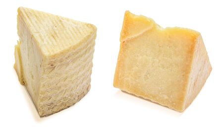 Cured sheep cheese (manchego type). Two wedges and portions. Isolated on white background.