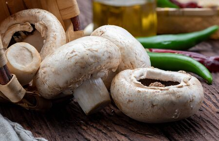 Basket of mushrooms (champignon, cut feet, Agaricus Bisporus) raw (uncooked). With several ingredients (olive oil, garlic and chilli pepper). Wood background and home appearance.