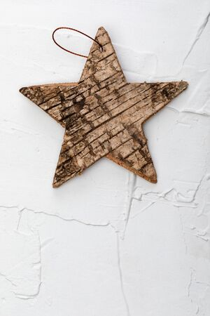 Beautiful star of birch bark on white textured background. Ready for Christmas greeting.