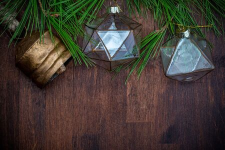 Delicate glass Christmas ornaments and natural branches of pine (spruce) on wooden background. Ready for Christmas greeting. Фото со стока