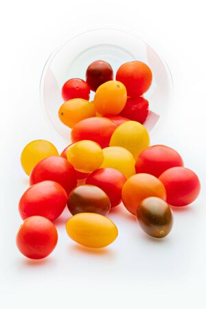 Colorful cherry tomatoes (red, garnet and yellow), fresh and raw. In plastic jar. Isolated on white background Фото со стока
