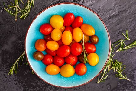 Bowl of colorful cherry tomatoes (red, garnet and yellow), fresh and raw. With water drops and rosemary. On black textured background and space to insert text (copy space). Top View