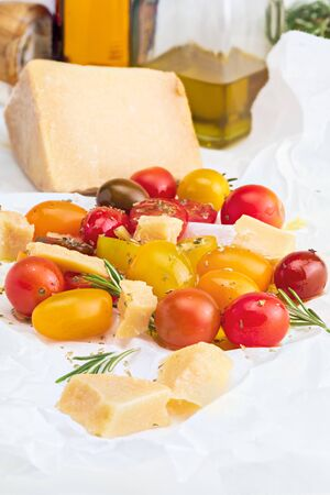 Colorful cherry tomatoes (red, garnet and yellow), fresh and raw with sheep cheese. With drops of water and rosemary. Homemade and rustic look with olive oil and spices. Front View