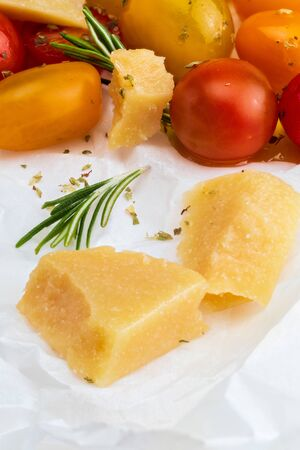 Close-up of sheep cheese with rosemary and cherry colored tomatoes (red, garnet and yellow), fresh and raw. Homemade and rustic look with olive oil and spices. Фото со стока