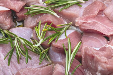 Raw and fresh (diced) pieces of turkey meat (chicken). With rosemary branches (spices). Фото со стока