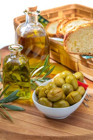 Artisan olives (canned in extra virgin olive oil, vinegar, spices) with red peppers and garlic. Includes olive tree leaves, slices of bread and bottle of extra virgin olive oil. Appetizer concept. On wooden board background. Фото со стока