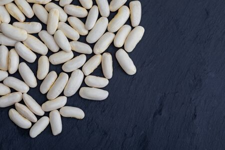 White beans (fabes) raw (legume) on black slate background with texture. With space to insert your text here.