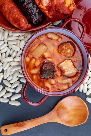 Appetizing spoon dish. Delicious for autumn, winter and all year. Asturian fabada, typical dish of Asturias (Spain). Stew of beans (white beans) with chorizo, bacon, black pudding, bacon, onion, garlic, parsley and salt. Фото со стока