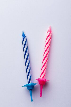 2 birthday candles on white background. For birthday greeting card. Space to insert text. Very colorful, with blue, red, yellow and white. For birthday greeting card. Фото со стока