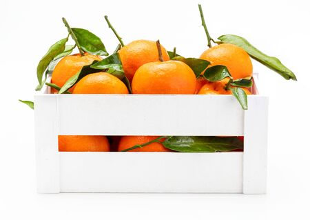 Fresh and raw tangerines with green leaves in wooden box. Isolated on white background.