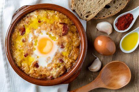 Knoblauch-Brot-Suppe (Kastilisch, aus Spanien) im Tontopf und seine Hauptzutaten. Von oben betrachten. Holzhintergrund