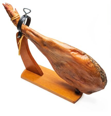 Whole leg of Spanish Iberian serrano ham in wooden support (jamoneror). Isolated on white background.