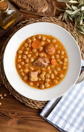 Chickpea stew dish (potage - cocido madrileño). With beef, sausage (chorizo), bacon, carrots and olive oil. Rustic appearance. Top view.