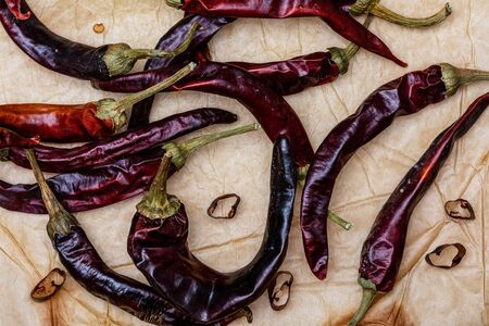 Set of dried red chillies (whole and cut) (spices collection). On rustic background. Фото со стока