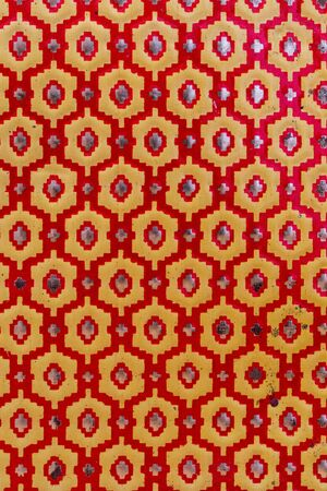 Metallic texture of red and yellow hexagons. Pattern. Retro look, old and shiny.