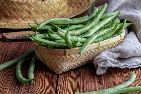 Fresh and raw green beans (green round beans) in wicker basket. Rustic and homemade look on wooden background. Фото со стока - 134588549