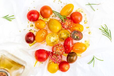 Colorful cherry tomatoes (red, garnet and yellow), fresh and raw. With drops of water and rosemary. Homemade and rustic look with olive oil and spices. Top View Фото со стока