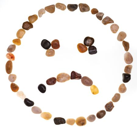 Emoji (emoticon) of sad face handmade with stones (boulders). Isolated on white background. Collection made with stones.