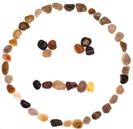 Emoji (emoticon) of neutral face (poker face) handmade with stones (boulders). Isolated on white background Collection made with stones.
