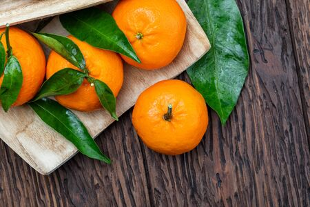 Fresh and raw tangerines with green leaves. Rustic appearance. On wooden background.