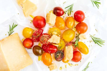 Colorful cherry tomatoes (red, garnet and yellow), fresh and raw with sheep cheese. With drops of water and rosemary. Homemade and rustic look with olive oil and spices. Top View