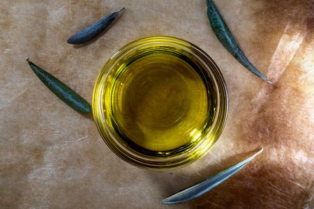 Extra virgin olive oil in glass bowl. It includes olive leaves. Rustic Background. Top view. Фото со стока - 135007632