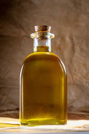 Extra virgin olive oil in glass bottle. Rustic Background. Front view. Фото со стока - 135007630