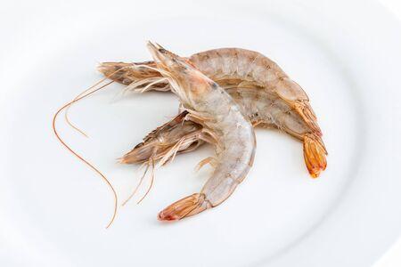 Close-up of fresh, raw and whole prawns. On white background. Фото со стока