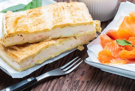Salmon pie and fresh cheese (puff pastry). With natural ingredients. Home and rustic appearance.