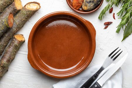 Empty clay pot. On white wooden background. Of rustic aspect it includes spices (rosemary, laurel, chilli peppers) and cutlery. Concept to include your food and your text.
