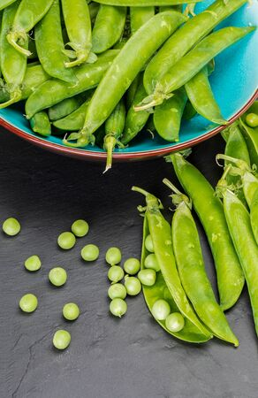 Green, tender, fresh and raw peas. Close-up and top view. Rustic appearance. Rustic appearance. Black background. Фото со стока