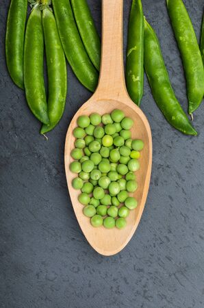 Green, tender, fresh and raw peas. Close-up and top view. Rustic appearance. Rustic appearance and wooden spoon. Black background. Фото со стока