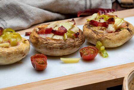 Delicious mushrooms (champignon, foot cut, Agaricus Bisporus) cooked and stuffed (bacon, tomato, garlic, pepper, ...). Close up.