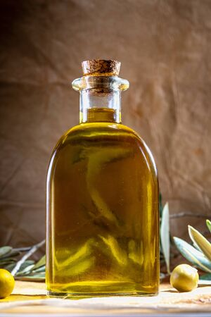 Extra virgin olive oil in glass bottle. It includes olive leaves and branches. Rustic Background. Front view.