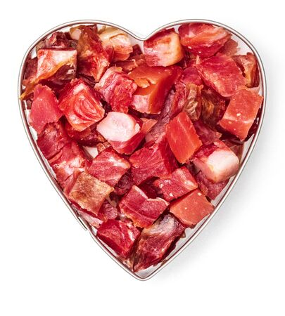 Iberian ham (serrano) cut into cubes (diced). Heart-shaped. Passion for ham. Isolated on white background.