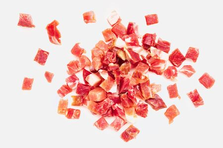 Iberian ham (serrano) cut into cubes (diced). Isolated on white background. 版權商用圖片