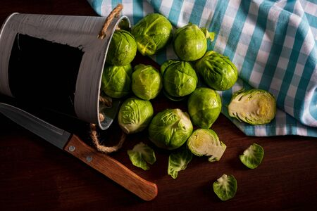 Raw, fresh, whole and cut brussels sprouts (cabbages - Brassica oleracea). Rustic and homemade appearance.