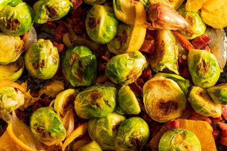 Cooked brussels sprouts (cabbages) with ham, garlic, oil and orange. Rustic and homemade looking recipe. 版權商用圖片