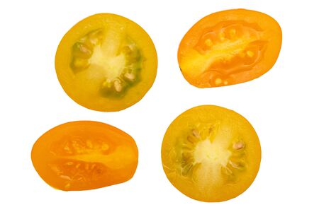 Fresh and raw yellow cherry tomatoes, cut in half. With water drops. Isolated on white background.