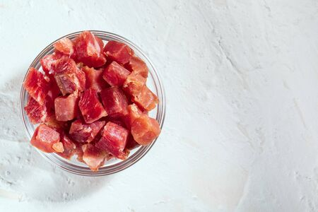 Iberian ham (serrano) cut into cubes (diced). In a glass bowl. White textured background. Copy space.