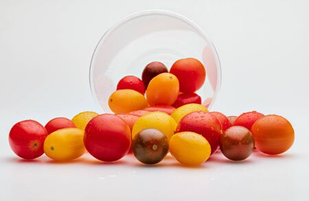 Colorful cherry tomatoes (red, garnet and yellow), fresh and raw. In plastic jar. Isolated on white background 版權商用圖片