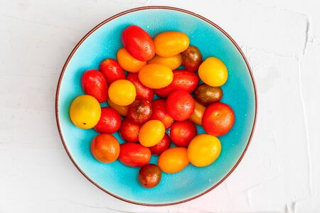 Bowl of colorful cherry tomatoes (red, garnet and yellow), fresh and raw. With water drops On white textured background and space to insert text (copy space). Top View