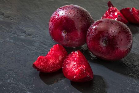 Appetizing and healthy red plums, whole and cut into segments with a rustic appearance on a black background.