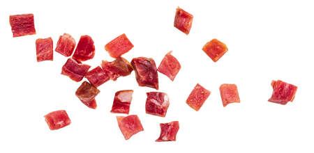 Iberian ham (serrano) cut into cubes (diced). Isolated on white background. Фото со стока