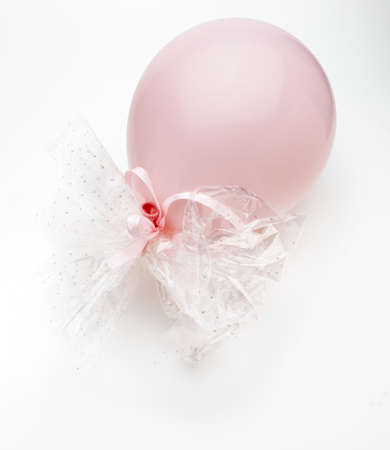 Pink balloon with delicate white bows. Isolated on white background. Фото со стока