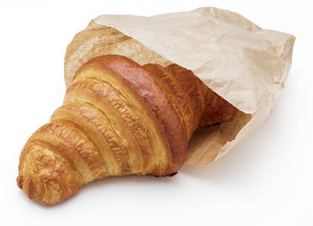 Crispy fresh butter croissant. In a paper bag. Isolated on white background. Фото со стока