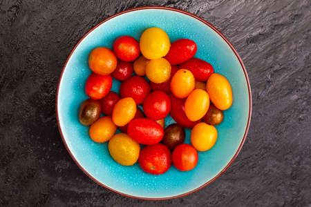 Bowl of colorful cherry tomatoes (red, garnet and yellow), fresh and raw. With water drops. On black textured background and space to insert text (copy space). Top View Фото со стока